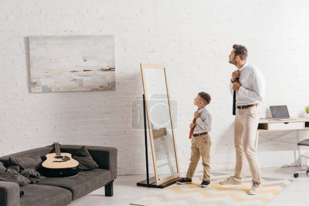 Photo for Full length view of son and father in formal wear standing near mirror - Royalty Free Image
