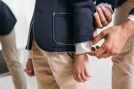 Photo pour Vue partielle de papa aidant son fils à s'habiller à la maison - image libre de droit