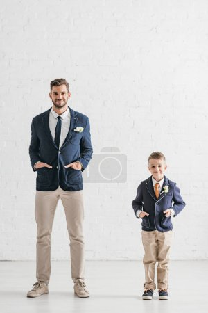 full length view of father and son in jackets with boutonnieres standing with hands in pockets