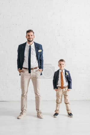 Photo pour Vue pleine longueur du père et du fils dans des vestes avec des boutonnières - image libre de droit
