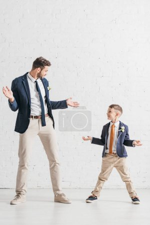 Photo for Full length view of father and son in jackets with boutonnieres looking at each other - Royalty Free Image