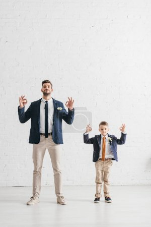 Photo for Full length view of father and son in jackets with boutonnieres showing okay signs - Royalty Free Image