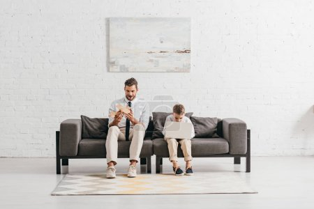 Photo for Dad with toy plane and son with laptop sitting on sofa - Royalty Free Image