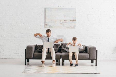Photo pour Papa et fils dans l'usure formelle utilisant des ordinateurs portatifs tout en s'asseyant sur le sofa - image libre de droit