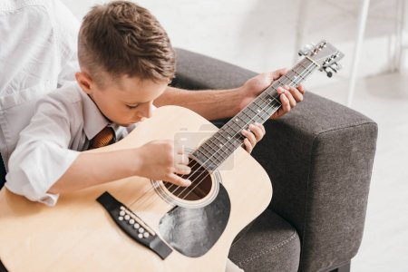 Photo for Cropped view of dad teaching son to play acoustic guitar at home - Royalty Free Image