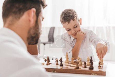 Photo pour Foyer sélectif de papa et fils jouant aux échecs ensemble à la maison - image libre de droit