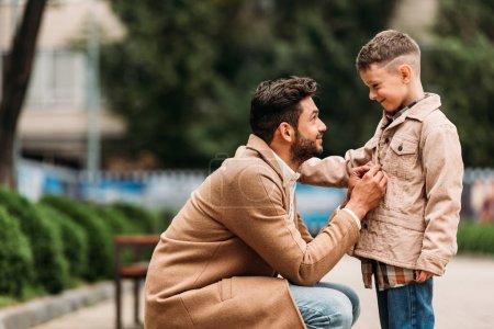 Photo pour Vue de côté de papa dans le manteau et le fils dans la veste sur la rue en jour d'automne - image libre de droit
