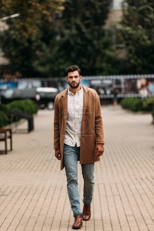 Photo for Full length view of handsome bearded man in stylish coat in autumn day on street - Royalty Free Image