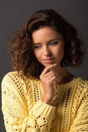 Photo pour Femme bouclée rêveuse en pull tricoté jaune sur fond noir - image libre de droit