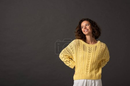 happy curly woman in yellow knitted sweater looking away on black background