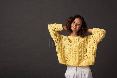Photo pour Femme bouclée de sourire dans le chandail tricoté jaune avec des mains derrière la tête sur le fond noir - image libre de droit