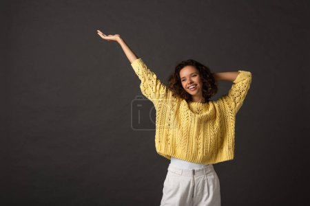 Photo for Smiling curly woman in yellow knitted sweater with hands in air on black background - Royalty Free Image