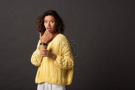 Foto de Mujer rizada sorprendida en suéter de punto amarillo sosteniendo el café para ir en el fondo negro - Imagen libre de derechos