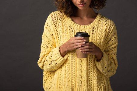 Foto de Vista recortada de la mujer en suéter de punto amarillo sosteniendo café para ir sobre fondo negro - Imagen libre de derechos