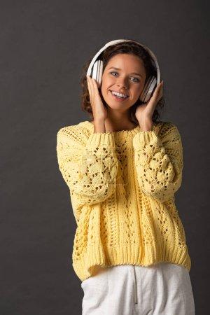 Photo pour Femme bouclée souriante en chandail tricoté jaune écoutant de la musique dans des écouteurs sur fond noir - image libre de droit