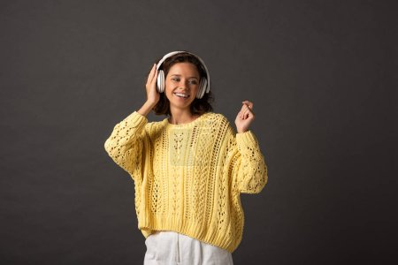 Photo for Smiling curly woman in yellow knitted sweater listening music in headphones on black background - Royalty Free Image