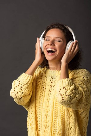 happy curly woman with closed eyes in yellow knitted sweater listening music in headphones on black background