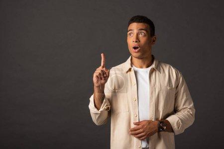 Photo pour Beau homme métis en chemise beige montrant geste idée sur fond noir - image libre de droit