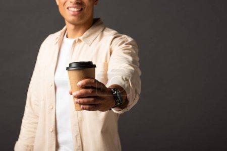 Photo pour Vue recadrée de l'homme mélangé de course dans le café de fixation de chemise beige pour aller sur le fond noir - image libre de droit