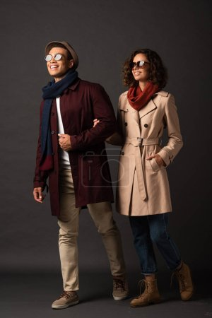 Photo pour Heureux élégant couple interracial en tenue d'automne tenant la main sur fond noir - image libre de droit