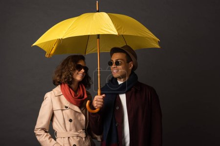 Photo for Smiling stylish interracial couple in autumn outfit holding yellow umbrella on black background - Royalty Free Image