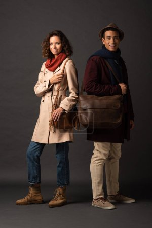 Photo for Smiling stylish interracial couple in autumn outfit with bags on black background - Royalty Free Image