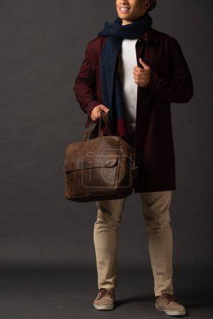 Photo pour Vue recadrée de sourire homme de race mixte en écharpe et chapeau tenant sac marron en cuir sur fond noir - image libre de droit