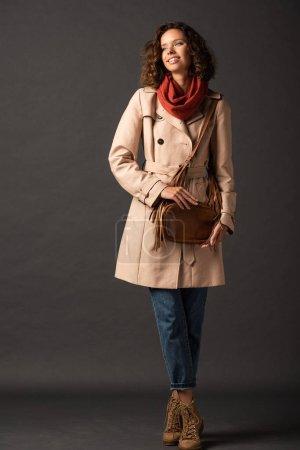 Photo pour Femme élégante de sourire dans le trench-coat et l'écharpe regardant loin sur le fond noir - image libre de droit