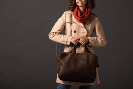 Photo for Cropped view of stylish woman in trench coat and scarf holding leather brown bag on black background - Royalty Free Image