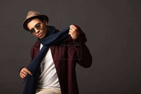elegant mixed race man in scarf, sunglasses and hat on black background