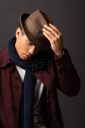 mixed race man in scarf holding hat on black background
