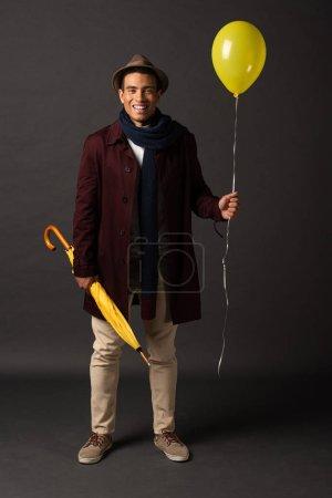 Photo pour Homme de race mixte souriant en écharpe et chapeau tenant ballon jaune et parapluie sur fond noir - image libre de droit