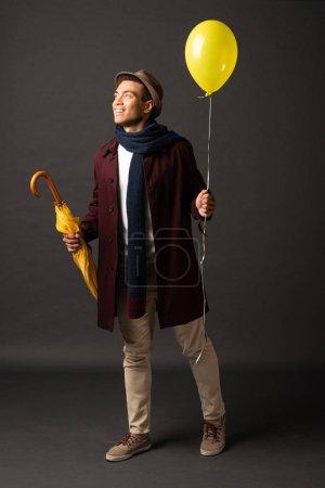 Photo pour Homme de race mixte souriant en écharpe et chapeau tenant ballon jaune et parapluie et regardant loin sur fond noir - image libre de droit