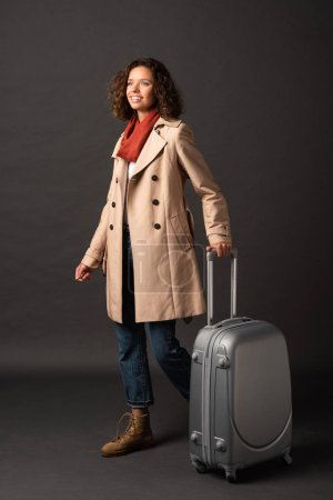 Photo for Smiling elegant woman in trench coat and scarf holding handle of suitcase on black background - Royalty Free Image