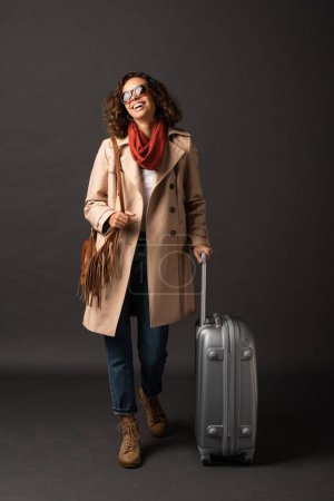 Photo for Laughing woman in trench coat, sunglasses and scarf holding handle of suitcase on black background - Royalty Free Image