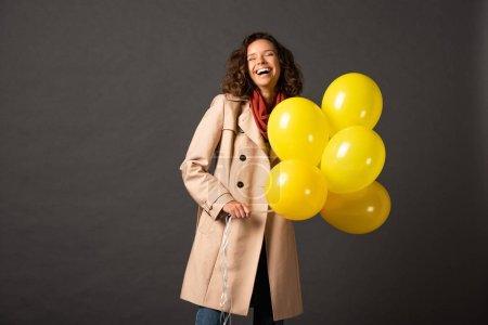 Photo pour Femme bouclée riante en trench coat tenant des ballons jaunes sur fond noir - image libre de droit