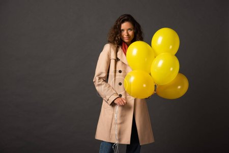 Foto de Mujer rizada en la capa de trinchera sosteniendo globos amarillos sobre fondo negro - Imagen libre de derechos