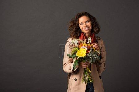 Photo pour Femme bouclée de sourire dans le bouquet de fixation de trench-coat des fleurs sauvages automnales sur le fond noir - image libre de droit