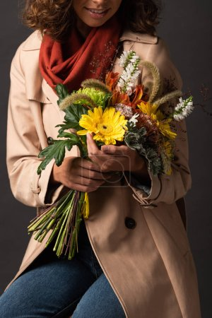 Photo for Cropped view of woman in trench coat holding bouquet of autumnal wildflowers on black background - Royalty Free Image