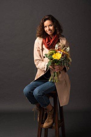 Photo pour Femme bouclée de sourire dans le trench-coat s'asseyant sur la présidence avec le bouquet des fleurs sauvages automnales sur le fond noir - image libre de droit