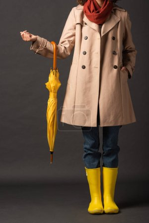 Photo for Cropped view of woman in trench coat and rubber boots holding yellow umbrella on black background - Royalty Free Image