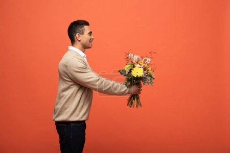 Foto de Vista lateral de la sonrisa hombre de raza mixta regalo de ramo de otoño aislado en naranja - Imagen libre de derechos