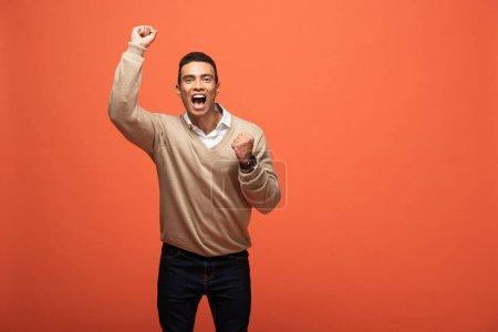 Photo pour Homme heureux de course mélangé dans le chandail beige affichant le geste de oui isolé sur l'orange - image libre de droit