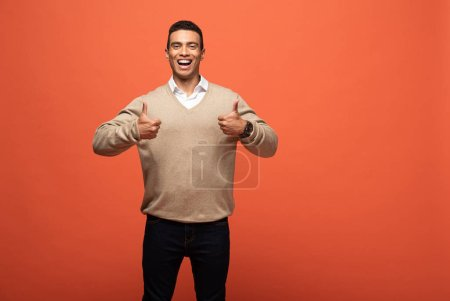 happy mixed race man in beige sweater showing thumbs up isolated on orange
