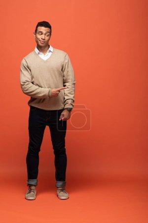 Photo pour Homme mélangé de course dans le chandail beige pointant avec le doigt de côté isolé sur l'orange - image libre de droit