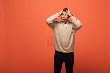 Foto de Sorprendido hombre de carrera mixto en suéter beige sosteniendo la cabeza aislada en naranja - Imagen libre de derechos
