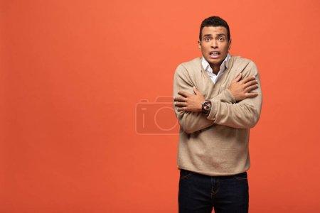 Photo pour Confus mixte homme en pull beige se sentant froid isolé sur orange - image libre de droit