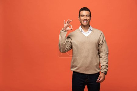 Photo for Happy mixed race man in beige sweater showing ok sign isolated on orange - Royalty Free Image