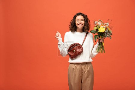 Photo for Happy woman in autumnal outfit holding bouquet of flowers isolated on orange - Royalty Free Image