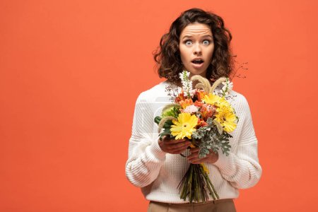 Photo for Shocked woman in autumnal outfit holding bouquet of flowers isolated on orange - Royalty Free Image